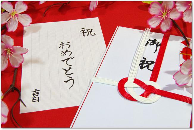 赤い背景に置かれた桜柄の入学祝いののし袋