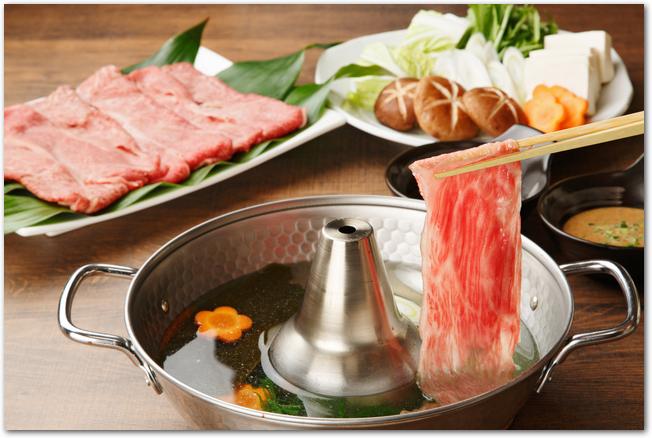 しゃぶしゃぶ用の鍋に具材と豚肉を入れている様子