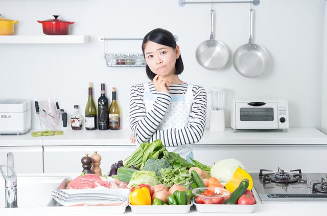 たくさんの食材を前にキッチンで悩む若い主婦の様子