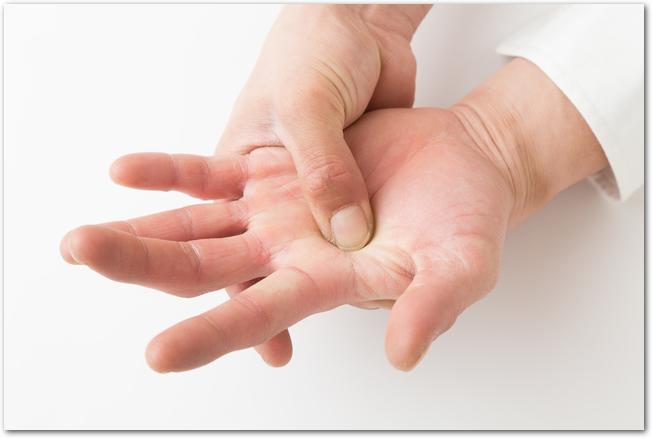 掌の中心にあるツボを押している男性の手元の様子