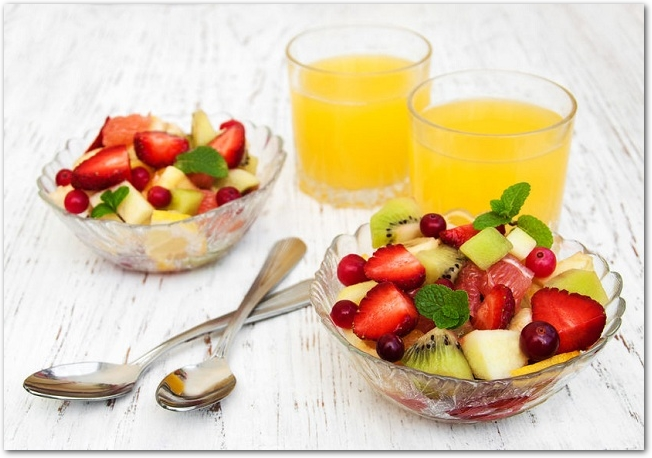オレンジジュースとガラスの器に盛られたフルーツ