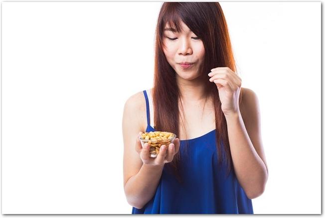 ナッツを食べている青い服を着た若い女性の様子