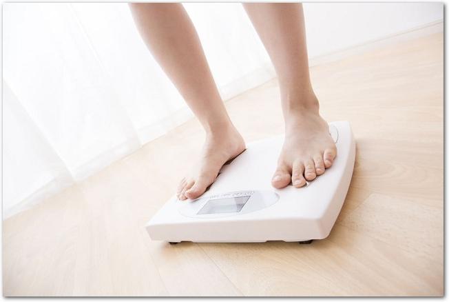 白い体重計に乗っている女性の足元の様子
