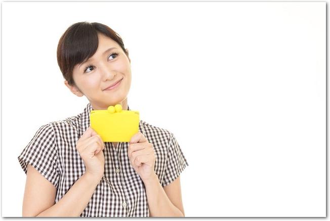 財布を持って斜め上を見る女性の様子