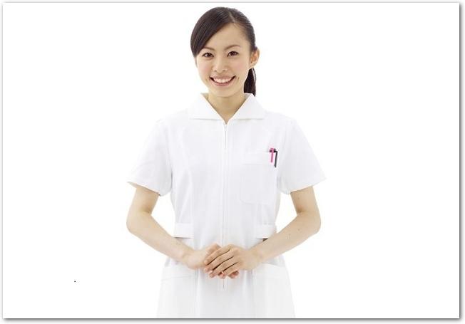 白背景の前に立つ白衣の女性看護師
