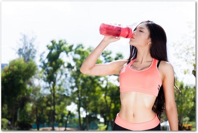 プロテインドリンクを飲むジョギング中の女性の様子