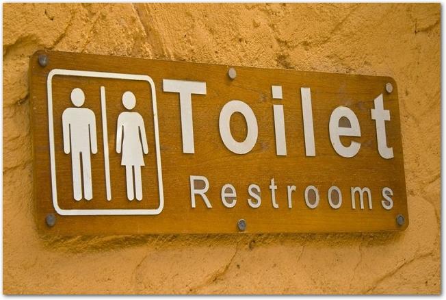 ピクトグラムが描かれた木製のトイレの案内板