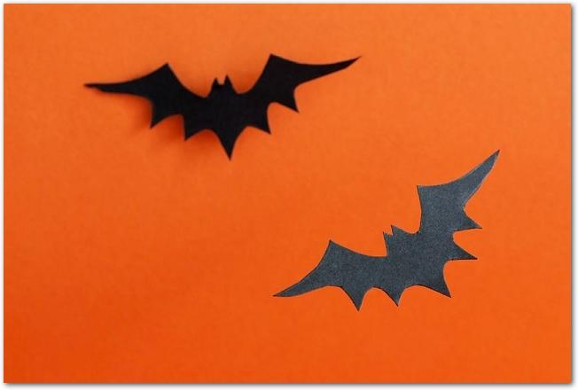 オレンジの背景に置かれた黒いコウモリの切り紙
