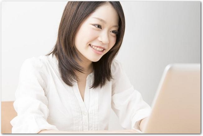 ノートパソコンを操作している笑顔の女性の様子