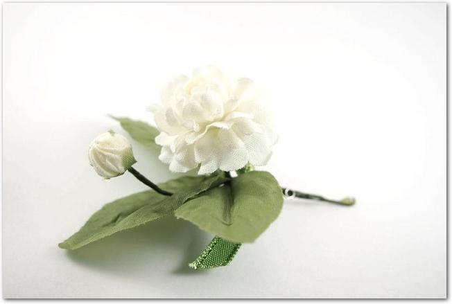 茎のある白い花のコサージュ
