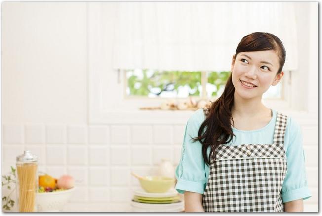 エプロン姿の女性がキッチンに立っている様子