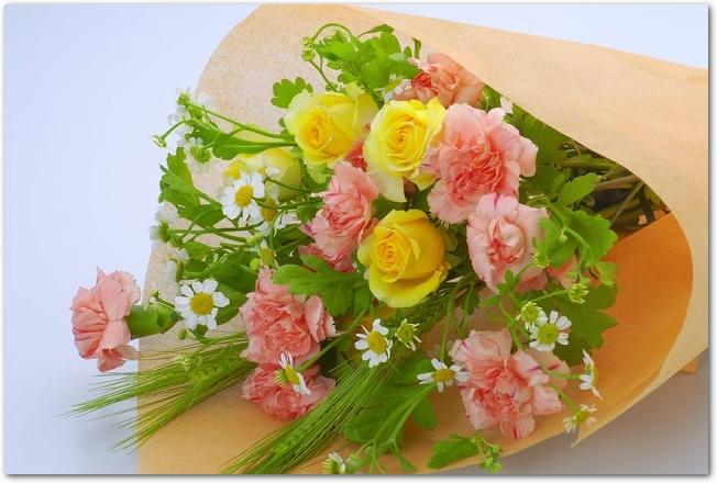 オレンジの紙でラッピングされたカーネーションの花束