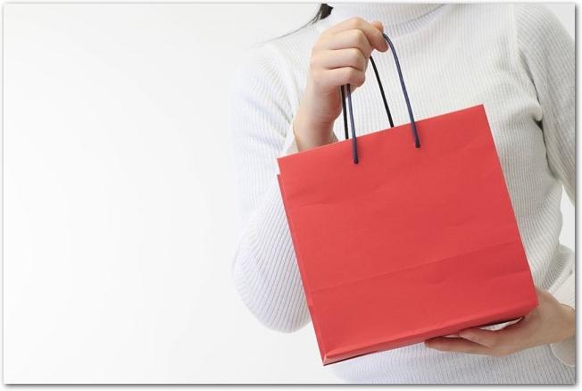 赤い紙袋を胸元で持つ女性の様子