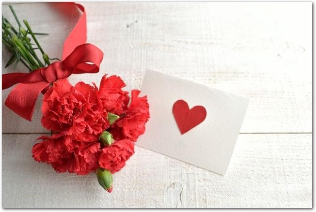 赤いハートの描かれたカードと赤いカーネーション
