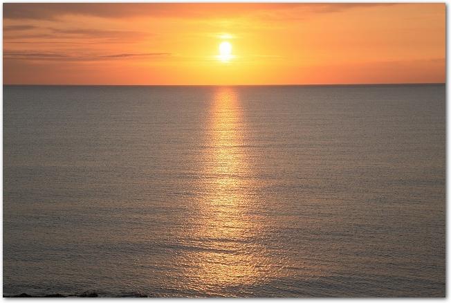 水平線の向こうから朝日が昇っている光景