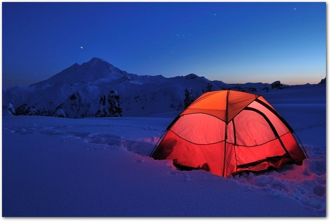 積雪の夜にテントを張ってキャンプをしている様子
