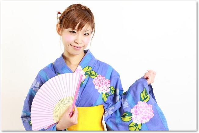 扇子を持つ青い浴衣姿の女性の様子