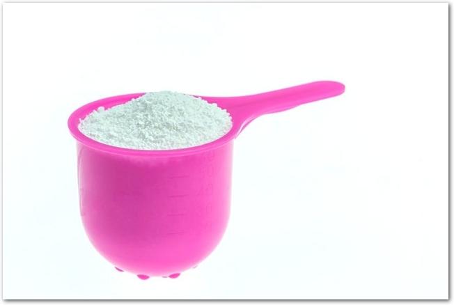 白い粉の入ったプラスチックのピンク色のスプーン
