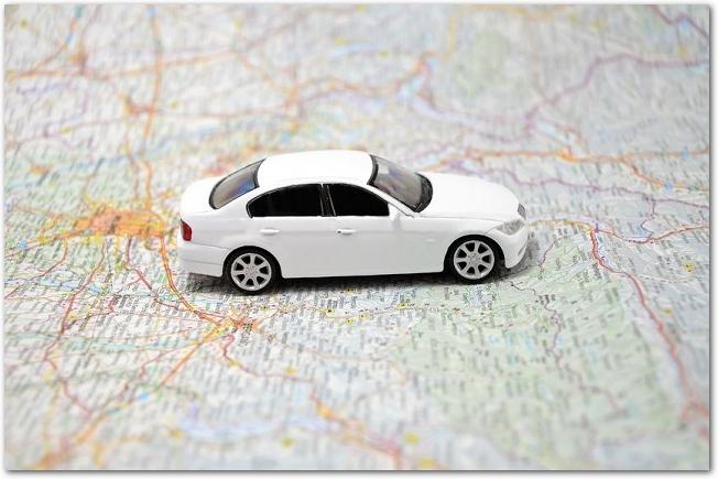 地図の上に白いミニカーが置いてある様子
