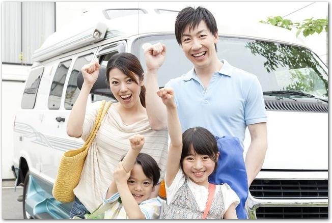 車の前でガッツポーズをする笑顔の家族の様子