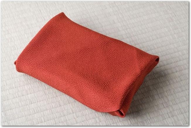 畳の上に赤い布の包みが置いてある様子